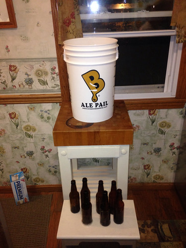 Fermenter of beer placed atop small table with bottles to be filled placed near the floor
