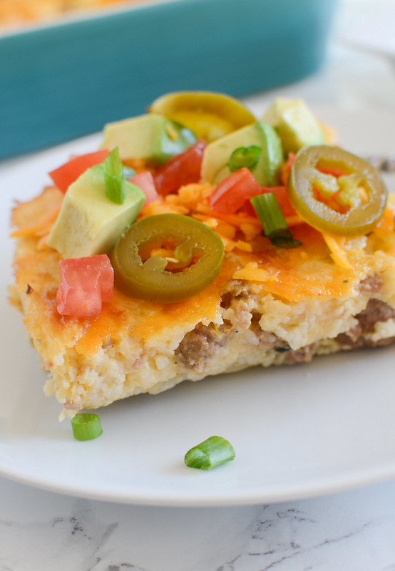 Loaded Grits Casserole - full of turkey sausage, sharp cheddar, green chiles and topped with avocado, tomatoes, green onions, and more!
