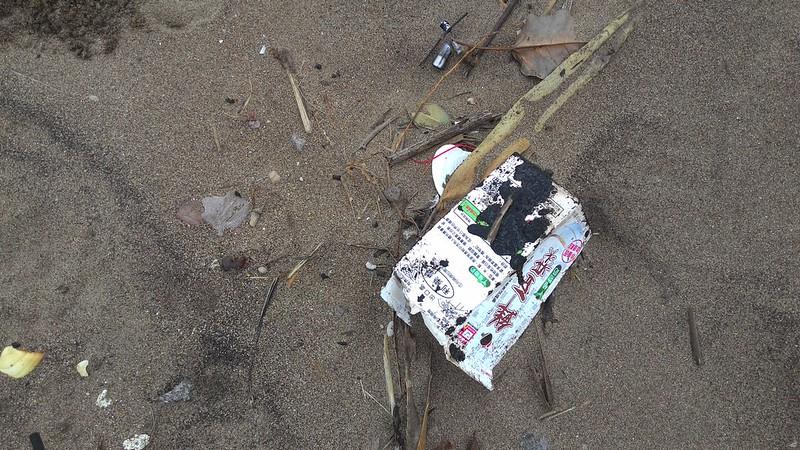 推判從石門飄來的飲料海廢,外包裝上黏油沾沙。攝影:林倩如。
