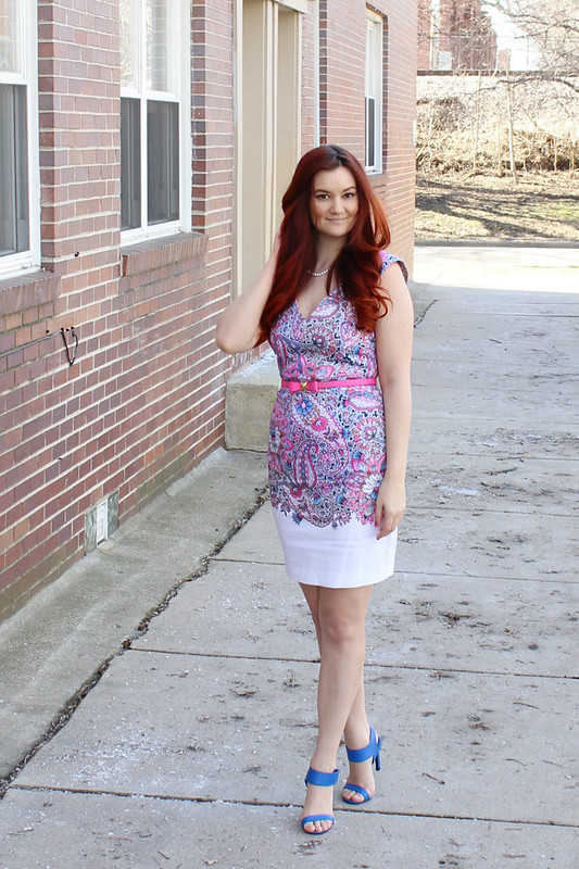 Standing in front of a brick building. Floral paisley printed dress in pink, purple, blue, and a white base. Kate Spade pink bow belt. Cobalt blue open toed heels.