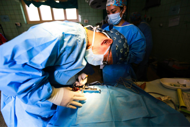 Bent on making a change: Chairman of The Smile Mission Vincent Yeow, who is also an internationally-renowned plastic surgeon, is pictured here intently working on a patient's face in the operating theatre. Photo credit: Smile Asia Facebook page