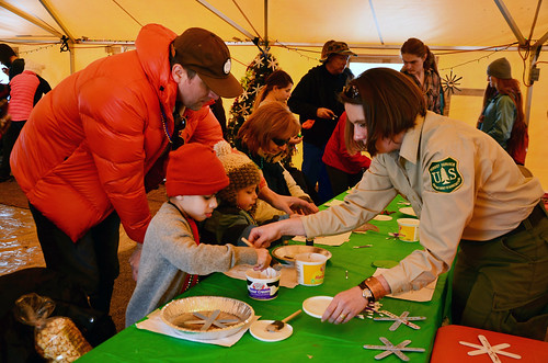 U.S. Forest Service employee Cheyenne Warner helping children make ornaments that will adorn the 2016 U.S. Capitol Christmas Tree