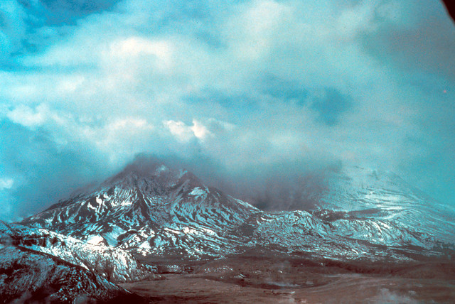 Image shows the hollowed-out remains of Mount St. Helens after the debris avalanche and eruption that removed nearly 2,000 feet of its summit. New snow has fallen, dusting the barren volcanic deposits. Partly cloudy skies blend into the steam rising from the empty crater. There is no dome yet.