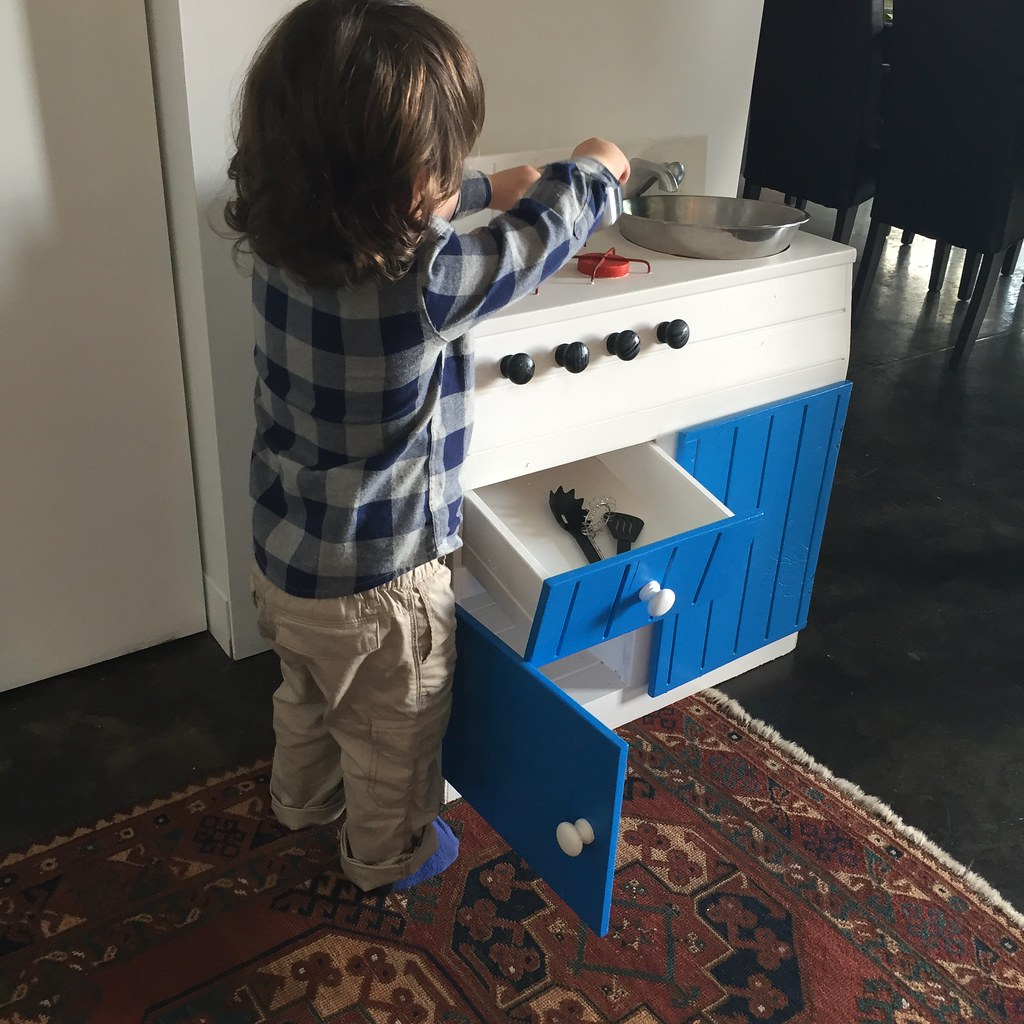 the same kitchen set, painted white with blue trim and silver sink features. new knobs on the front of the burners and cupboards too. being played with by an adorable two year old.