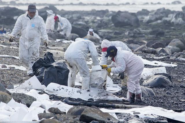 清污人員著防護衣、膠鞋、手套等拿杓子舀油,並進行垃圾分類。攝影:周昭蕊。