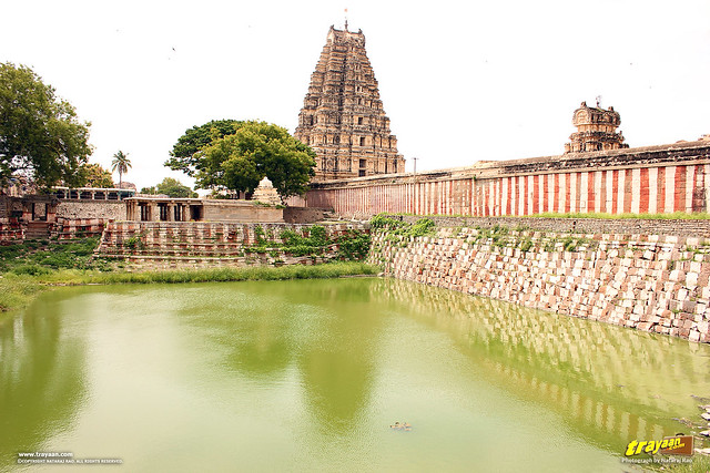 A view of Main entrance tower and the pond, known as the Manmatha Tank beside Virupaksha Temple complex, Hampi, Ballari district, Karnataka, India
