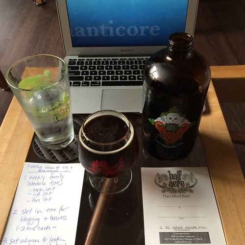 A close-up of a table containing: water, a snifter of beer, grumbler/howler, computer, a handwritten list, and a certificate for a free howler fill. Glass, howler, and certificate are all from Half Acre Beer Company in Chicago