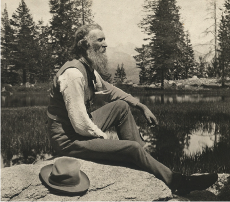 John Muir sitting on a rock