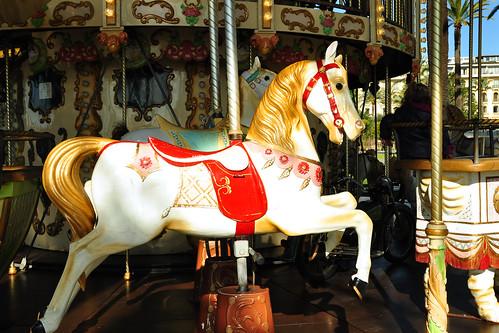 """Das Wort Karussell ist schon im Deutschen orthographisch nicht zu unterschätzen. Es kommt aus dem Arabischen """"kurradsch"""", das so etwas wie """"Spiel mit hölzernen Pferden"""" bedeutet. Wahrscheinlich die Grundidee der mittelalterlichen Ritterspiele mit Ringstechen: """"Sonntagischer Mercurius 1680, Woche 30, den 12. dieses ist das Corrusel gehalten ... denen zwölf turnirende Cavallieren ..."""". Noch beim Jahrmarktskarussell des 19. Jahrhunderts war das Greifen nach Ringen dabei, wovon noch heute Bezeichnungen wie """"Ringelreiten"""" und """"Ringelspiel"""" zeugen.  Bei der aktuellen deutschen Schreibweise muss man immer zuerst ein bisschen überlegen: 1 x r, 2 x s, 2 x l. Kommt man nach Frankreich, ist die Verwirrung komplett: 2 x r, 1 x s, 1 x l: carrousel. Fast jede französische Stadt, und sei sie auch noch so klein, besitzt so ein altes bzw. auf alt getrimmtes """"Carrousel"""". Und zwar unabhängig von Jahrmärkten. Die dortigen Carrousels stehen dauerhaft in Parkanlagen oder öffentlichen Gärten. Das besondere an ihnen ist, dass für jede Stadt ortsspezifische Bilder darauf gemalt sind. Hier z. B. in Nizza erkennt man ein Stück Nizza-Strandpromenade und eine Blumenverkäuferin des berühmten Nizzaer Blumenmarktes. Pferde, die ursprünglich ausschließliche Besatzung eines Karussells waren, sind heute nur noch nebenbei zu finden. Statt dessen gibt es Schweine, Dromedare, Raubkatzen und allerlei Fahrzeuge. Dieser kleine Nizzaer bewegt sich zielstrebig auf einen Flieger zu, Pferde und andere Tiere scheinen ihn nicht zu interessieren. Vielleicht ein zukünftiger Pilot? Foto Brigitte Stolle März 2016"""