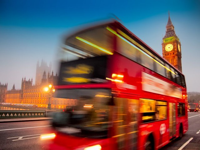 red-london-bus-driving-past-westminster-palace