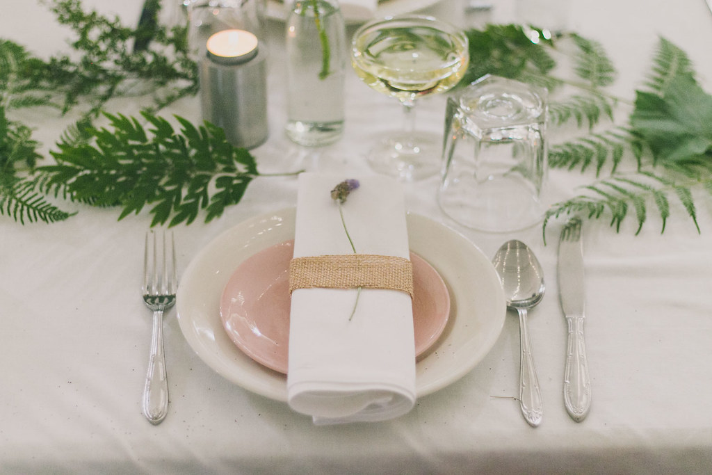 a vintage dinner plate, stacked with a vintage side plate, with a cloth napkin topped with a sprig of lavender