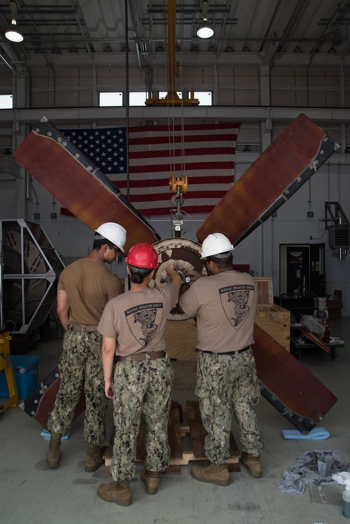 Sailors assigned to Naval Beach Unit (NBU) 7, perform maintenance on a fan blade of a landing craft air cushion (LCAC).
