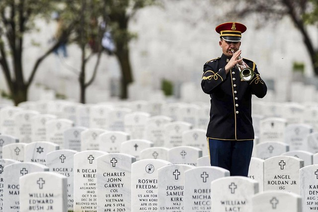 A lone Army bugler playing taps during an interment at Arlington National Cemetery