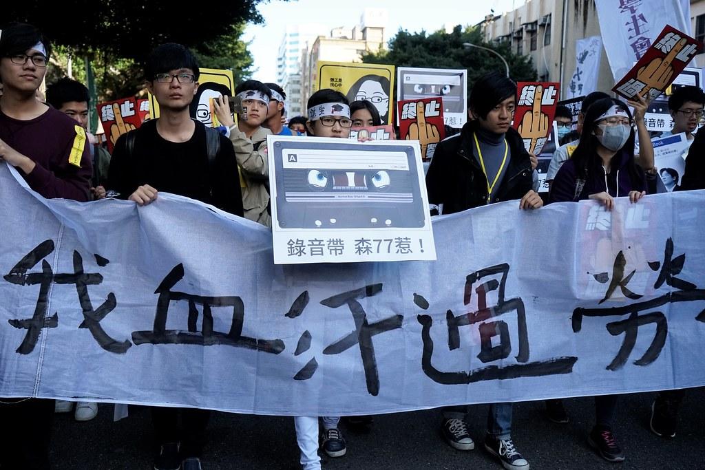 1223遊行中,有參與群眾拿著「錄音帶森77惹」的標語牌上街。(攝影:張宗坤)