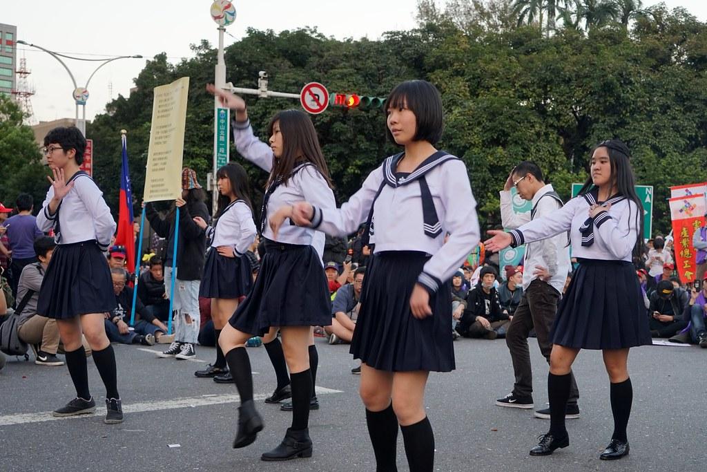 """1223下午的佔领现场,""""过劳功德会""""的""""劳坂46""""穿着水手服表演,成为一大亮点。(摄影:张宗坤)"""