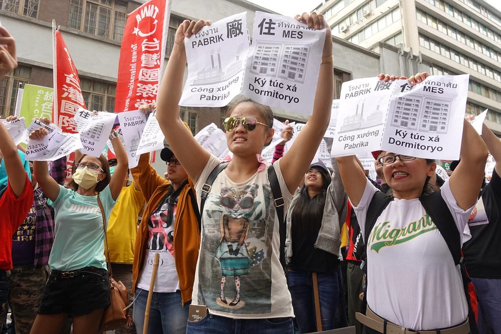 """移工在劳动部前把印有""""工厂""""和""""宿舍""""的纸张从中间撕破,象徵诉求""""厂住分离""""。(摄影:张智琦)"""