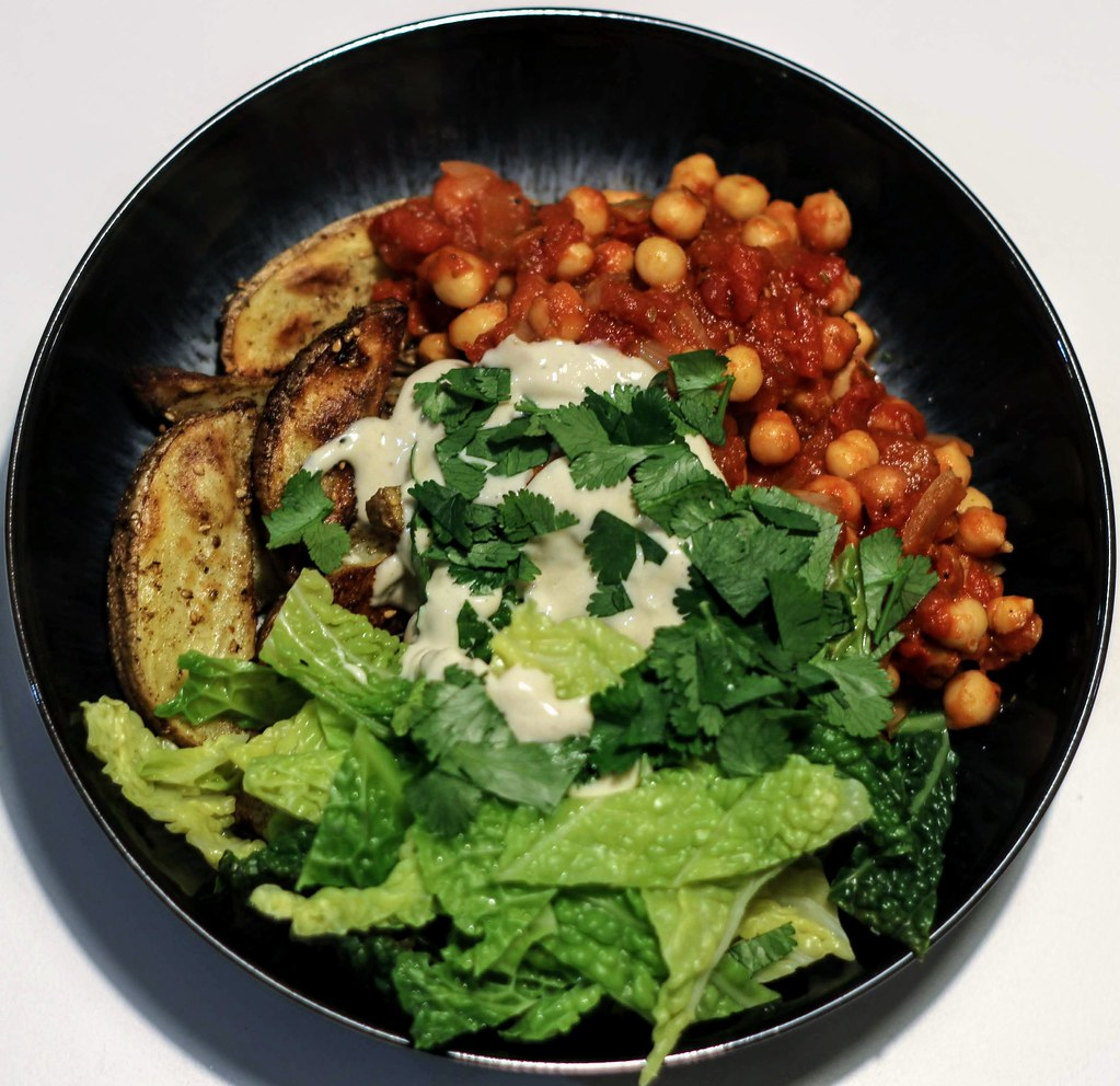 Wedges, greens and harissa chickpeas with a tahini sauce in bowl