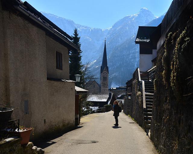 Paseando por las calles de Hallstatt con su precioso campanario y las montañas al fondo
