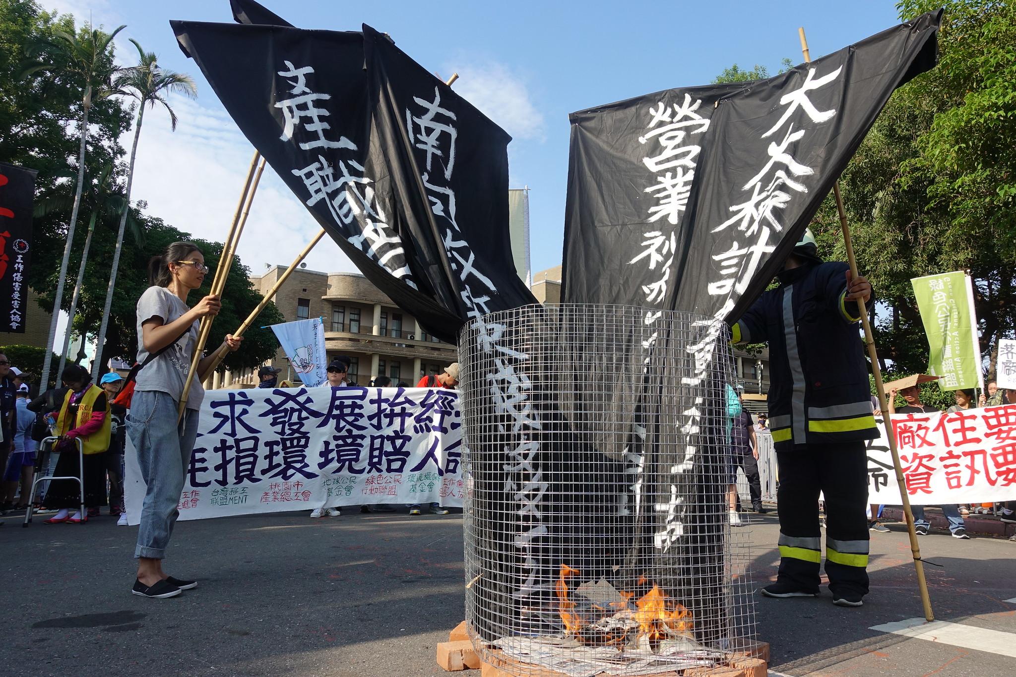 游行群众来到终点行政院,在政院前焚烧旗帜唿吁政府正视敬鹏大火烧出的问题。(摄影:张智琦)