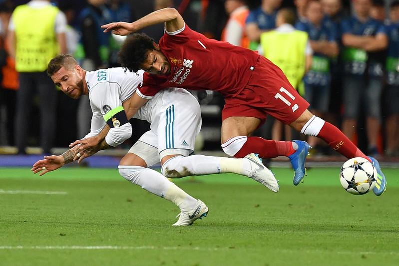 Mohamed Salah(圖右)在與Sergio Ramos(圖左)爭搶時倒地受傷。(AFP授權)