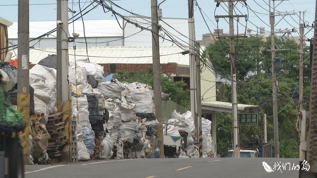 956-1-20一包包裝有資源回收物的太空包,疊了兩層,被堆置在資源回收場牆外