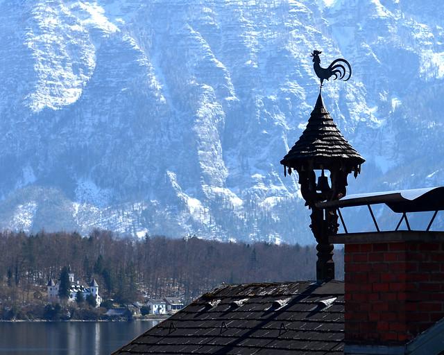 Veleta con forma de gallo con el castillo Grub al fondo en Hallstatt