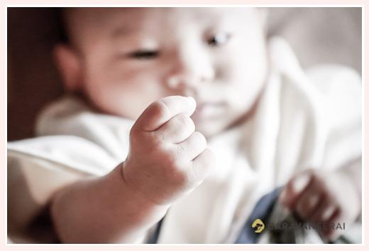 自分のげんこつをじっと見つめる赤ちゃん