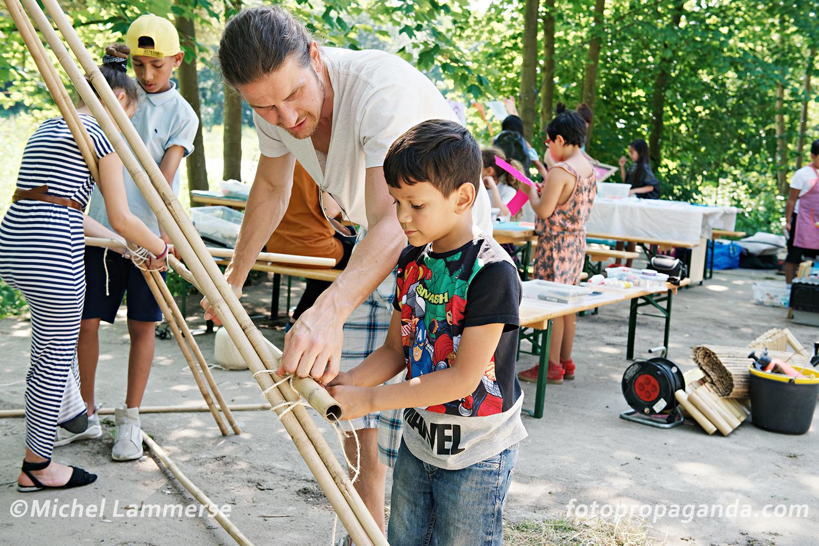 Kinderen bouwen mee aan de grote uitkijktoren van bamboe