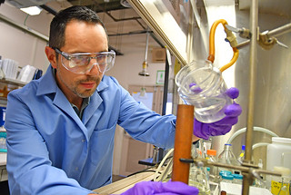 Photo of David Chavez working in his lab pouring example of melt-castable explosive into a copper mold