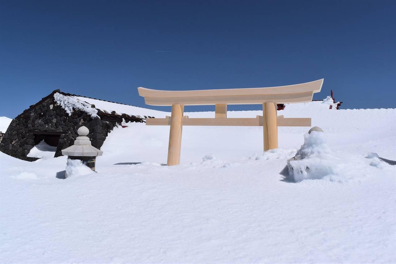 雪で埋まる富士山山頂の鳥居