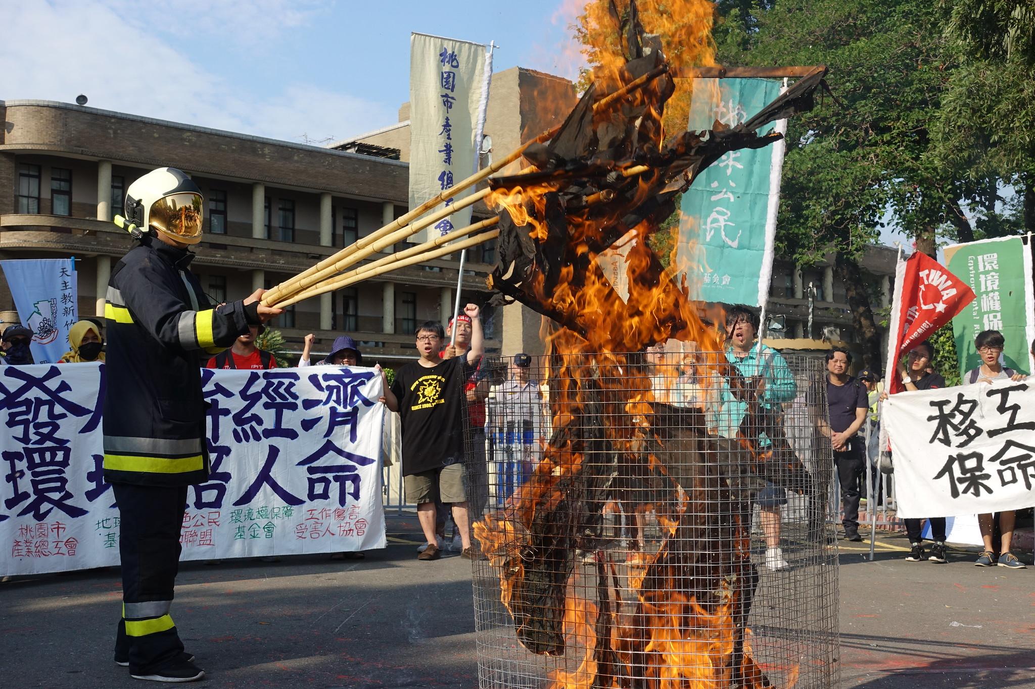 游行群众在行政院焚烧旗帜。(摄影:张智琦)