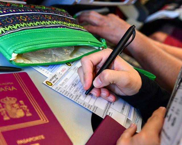Rellenando papeles de inmigración en el asiento del avión