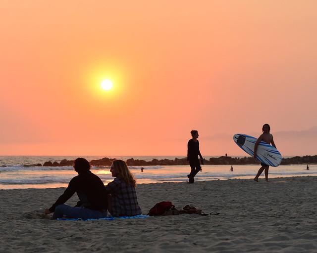 Pareja y surfistas al atardecer en las playas de Santa Monica