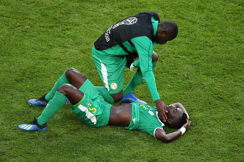 塞內加爾中場Idrissa Gana Gueye賽後躺在場上,隊友前來安慰。(AFP授權)