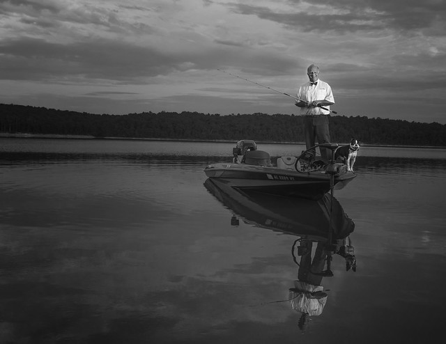 Bill Capps stands in his fishing boat with his dog.