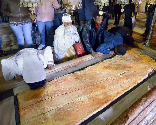 Personas rezando frente a la piedra del Santo Sepulcro