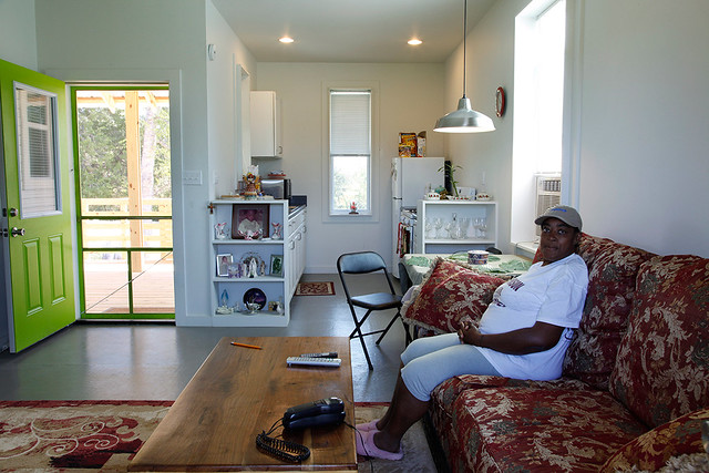 A woman sits inside a Rural Studio house.