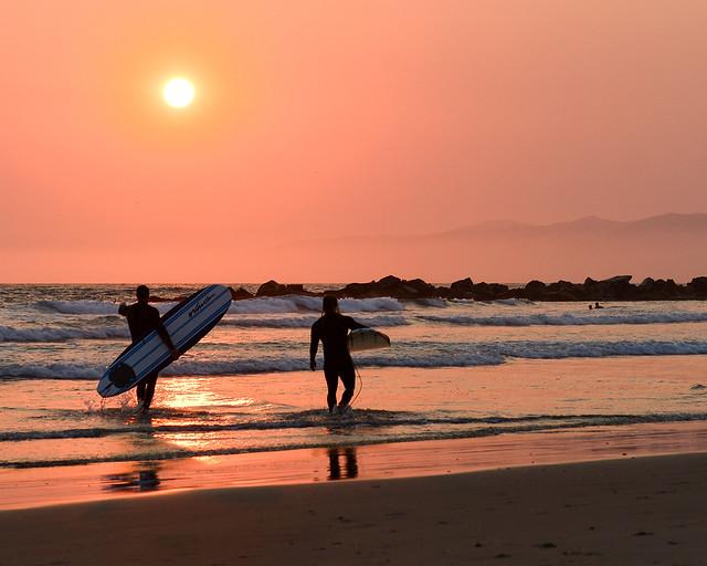 Surfistas con sus tablas en uno de los lugares más bonitos que ver en Los Angeles, Venice Beach