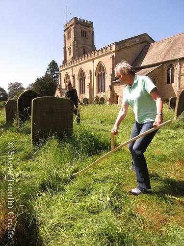 Scything among headstones in St John's churchyard, Yorkshire