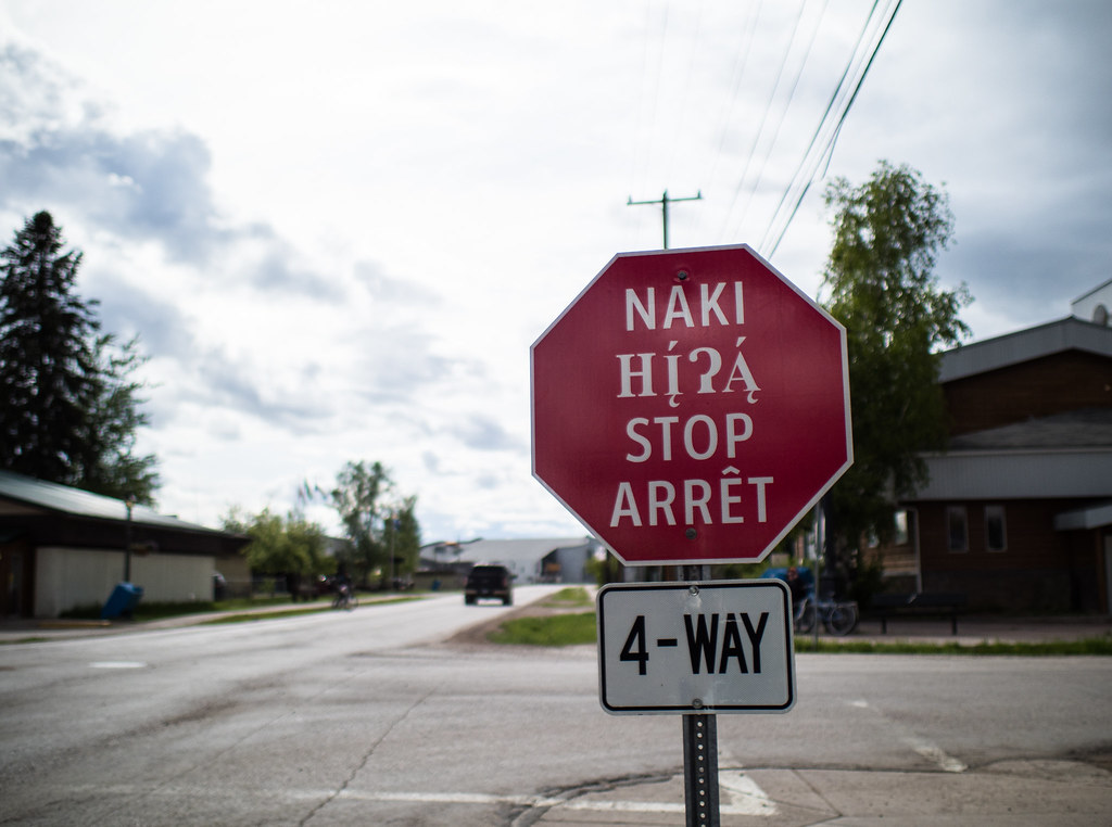 Stop sign in Fort Smith showcasing indigenous languages alongside French and English. Fort Smith, NWT. Louis Bockner/Sierra Club BC.
