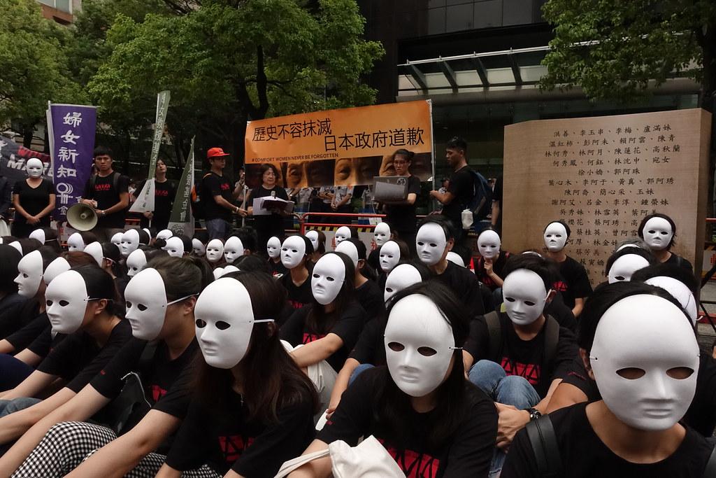 國際慰安婦日,民眾在日本台灣交流協會前穿戴面具靜坐抗議。(攝影:張智琦)