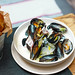 Mussels with onions and bacon in cream sauce in deep plate with bread on the table