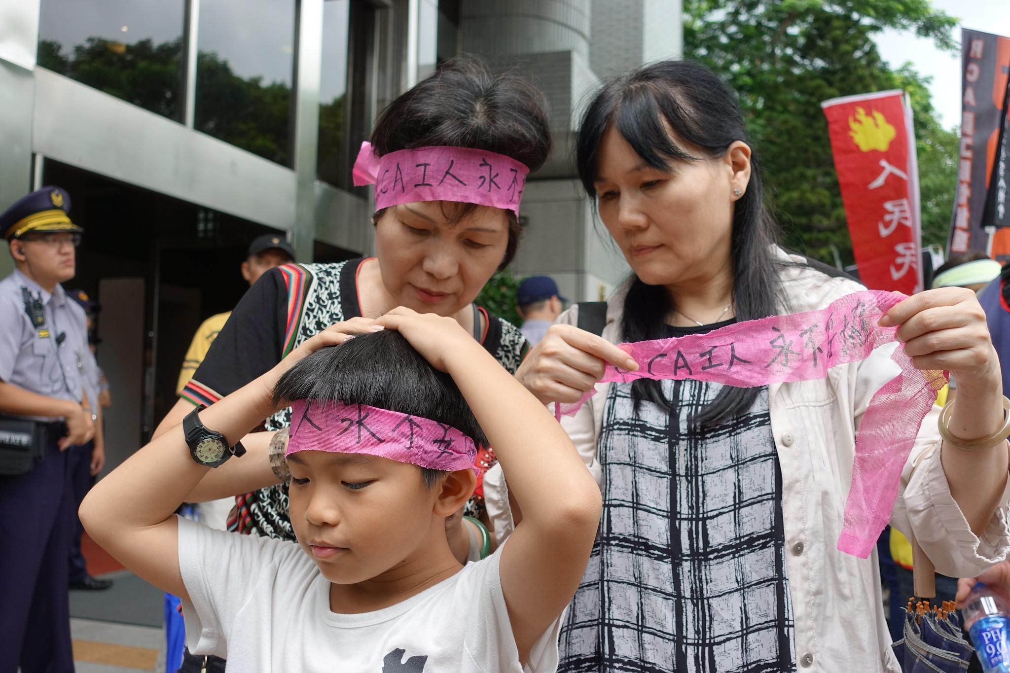 RCA員工為孩子別上「RCA工人永不妥協」的頭巾。(攝影:張智琦)