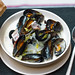 Mussels with onions and bacon in cream sauce in deep plate