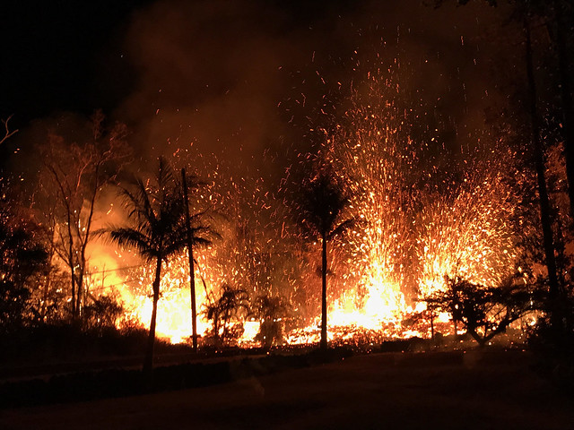 Image is a night view of the new Fissure 8: a curtain of white-orange lava sprays sparks into the night sky behind a silhoutte of palm trees.
