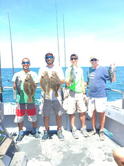 Photo of charter group holding their catch of flounder and black sea bass