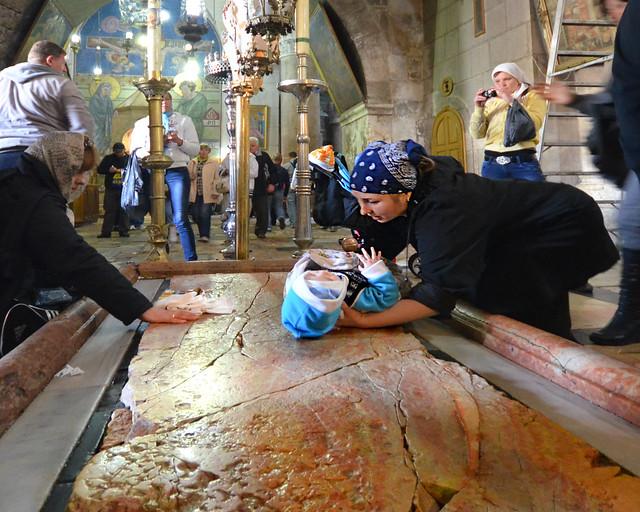 Mujer bendiciendo a su niño sobre la piedra de la unción