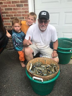 Photo of man and his grandsons with their bushel of crabs.