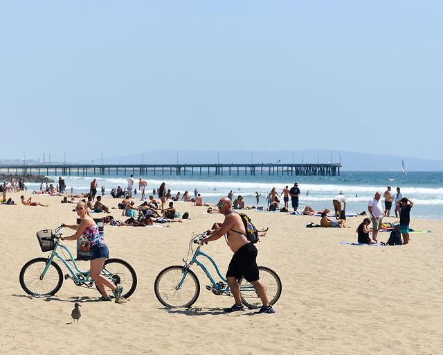 Gente con bicicletas por Venice Beach en Los Angeles