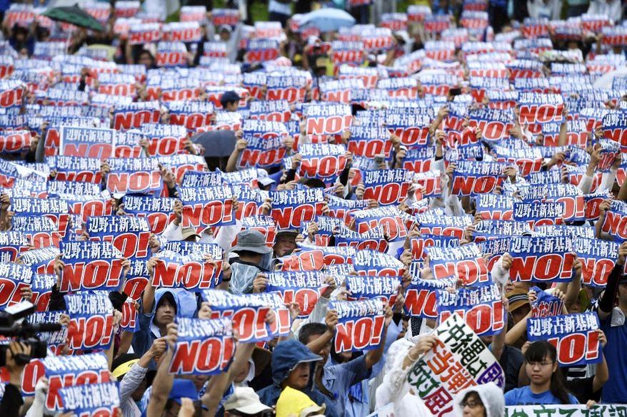 風雨之中,群眾高舉「邊野古基地 NO!」的標語。(Koji Harada/Kyodo News via AP)